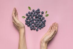 Fresh juicy blueberries with green leaves and female hands on pink background. Blueberries background. Flat lay top view. Healthy