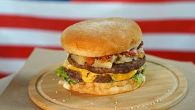 Fresh juicy burger with cheese, sauce and vegetables rotating on a wooden board in front of American Flag stock footage