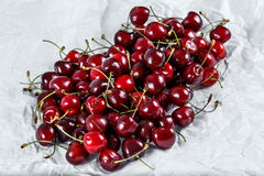 Fresh Juicy Cherries. scattered  on crumpled paper. Royalty Free Stock Images