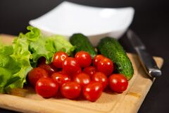 Fresh and juicy cherry tomatoes, cucumbers, gherkins, and lettuce leaves with water drops on a wooden cutting Board. Fresh vegetab