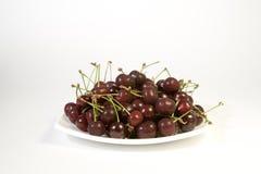Fresh juicy cherry on the white plate. Fresh juicy cherry in the plate on the white background Royalty Free Stock Photo