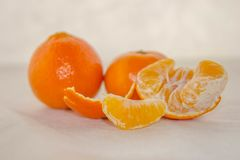 Fresh clementines on a white base. Fresh, juicy, fragrant clementine, husked, and in pieces on  a white based Stock Images
