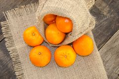 Clementines on a jute base with a wooden table Royalty Free Stock Images