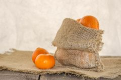 Clementine in a rustic bag on a wooden table. Fresh, juicy, fragrant clementine in a rustic bag on a wooden table and white background Royalty Free Stock Images