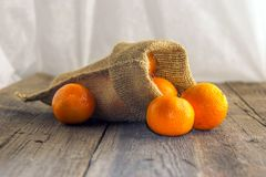 Clementine in a rustic bag on a wooden table. Fresh, juicy, fragrant clementine in a rustic bag on a wooden table and white background Stock Photos
