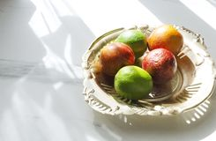 Fresh juicy fruits on the rustic metal tray, white marble table in the kitchen.Morning lights in the kitchen. Vertical shot of kitchen table in the morning stock images