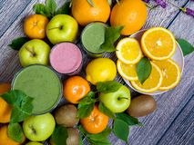 Fresh juicy fruits and smoothies on a wooden table. View from above. Detox and juicy fresh fruit on a wooden background. Healthy food royalty free stock image