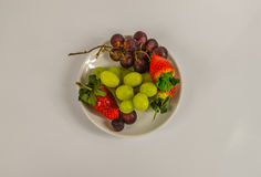 Fresh juicy fruits, strawberries, red grapes and white grapes Royalty Free Stock Photos