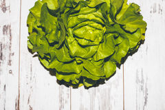 Fresh juicy green lettuce on vintage-styled table Stock Images