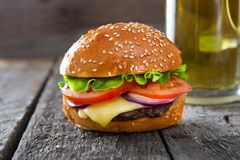 Fresh and juicy hamburger with a beer on wooden table stock image