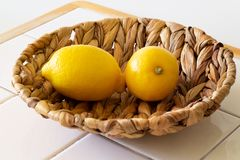 Two yellow lemons in rope bowl on white ceramic table and wooden and white background royalty free stock photography