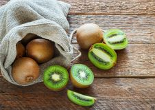 Fresh Kiwi fruit in bag on brown wooden background Royalty Free Stock Images