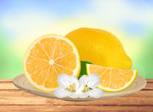 Fresh juicy lemon with green leaf and flowers on wood plate ov Stock Photos