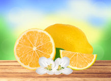 Fresh juicy lemon with green leaf and flowers on wooden table Stock Image