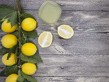 Fresh juicy lemons and a glass of homemade lemonade on a wooden background Royalty Free Stock Image