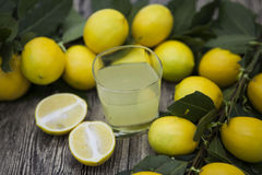 Fresh juicy lemons and a glass of homemade lemonade on a wooden background Royalty Free Stock Photos
