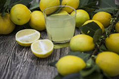 Fresh juicy lemons and a glass of homemade lemonade on a wooden background Stock Photo