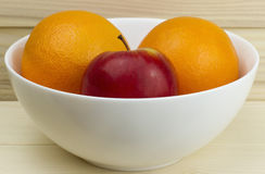 Fresh juicy natural apples and oranges in a shiny white plate on wooden background Stock Photos