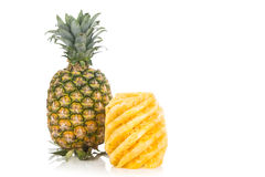 Fresh juicy nutritious cut pineapple with whole fruit as backgro Stock Photo