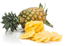 Fresh juicy nutritious cut pineapple with whole fruit as backgro Stock Photos