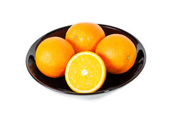 Fresh juicy oranges in black bowl Stock Image