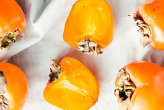 Fresh juicy persimmons on a light background, raw fruit Royalty Free Stock Photography