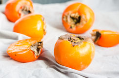 Fresh juicy persimmons on a light background, raw fruit Royalty Free Stock Photos