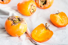 Fresh juicy persimmons on a light background, raw fruit Stock Images