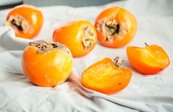 Fresh juicy persimmons on a light background, raw fruit Royalty Free Stock Image