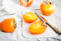 Fresh juicy persimmons on a light background, raw fruit Stock Photo