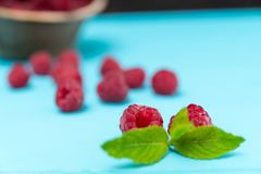 Fresh raspberries with mint leaf on blue table. Fresh juicy raspberries with mint leaf scattered on blue table stock photo