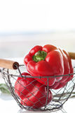 Fresh juicy red bell peppers in a crate on a white table on a sunny summer background Stock Photos