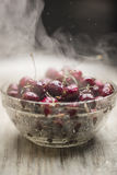 Fresh juicy ripe cherry covered with droplets of water lies in a transparent bowl on a light wooden background Stock Photos