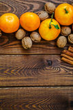 Fresh juicy ripe tangerines with leaves walnuts and cinnamon on wood Royalty Free Stock Image