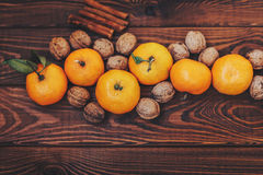 Fresh juicy ripe tangerines with leaves walnuts and cinnamon on wood Royalty Free Stock Photo