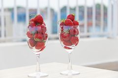 Fresh juicy strawberries in two transparent glass glasses for wine. Light background. Top view. Place for text. Beautiful red. Fresh juicy strawberries in two royalty free stock images