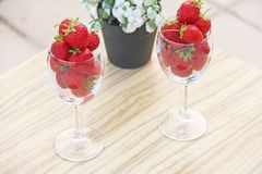 Fresh juicy strawberries in two transparent glass glasses for wine. Light background. Top view. Place for text. Beautiful red. Strawberry on a light background stock photos