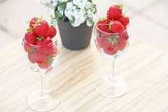 Fresh juicy strawberries in two transparent glass glasses for wine. Light background. Top view. Place for text. Beautiful red. Strawberry on a light background stock image