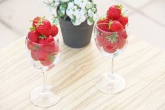 Fresh juicy strawberries in two transparent glass glasses for wine. Light background. Top view. Place for text. Beautiful red. Strawberry on a light background royalty free stock image