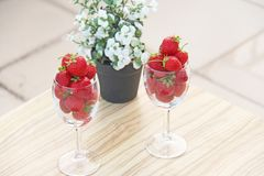 Fresh juicy strawberries in two transparent glass glasses for wine. Light background. Top view. Place for text. Beautiful red. Strawberry on a light background stock images