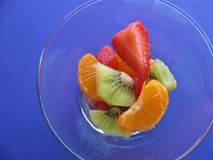 Fresh, juicy strawberry, kiwi and tangerine dessert. Luscious summer fruit in cocktail glass on ultra violet purple background, top view closeup Stock Photography