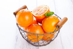 Fresh juicy summer blood oranges in a vintage basket with mint leaf on wooden table Stock Images