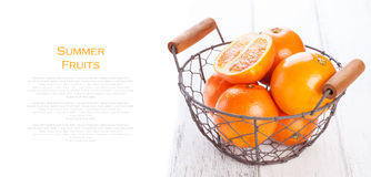 Fresh juicy summer blood oranges in a vintage basket with mint leaf on wooden table on a white background Royalty Free Stock Image