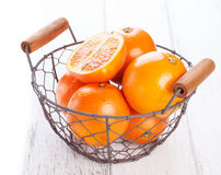 Fresh juicy summer blood oranges in a vintage basket with mint leaf on wooden table on a white background with copy space Royalty Free Stock Photography