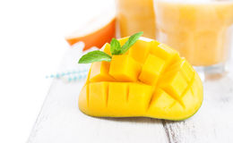 Fresh juicy summer cut mango, oranges and refreshment drinks on a wooden table on a white background, Royalty Free Stock Image