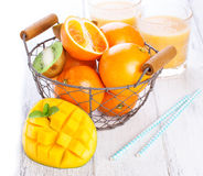 Fresh juicy summer fruits, oranges, mango, kiwi in a vintage basket and refreshment drinks on a wooden table on a white background Royalty Free Stock Photo