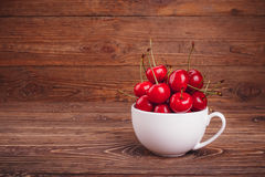 Fresh juicy sweet cherries in a white circle. Rustic wood background Royalty Free Stock Photo