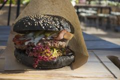 Fresh juicy tasty black burger with beef on wooden table in craf. T paper Royalty Free Stock Images