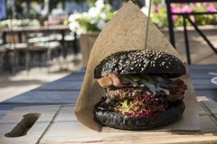 Fresh juicy tasty black burger with beef on wooden table in craf Stock Images