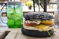 Fresh juicy tasty black burger with beef on wooden table in craf. T paper stock photography